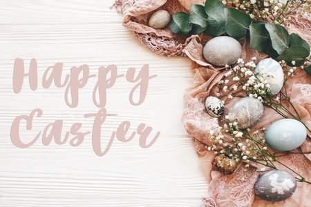 Photo for Happy Easter text sign on stylish easter eggs with spring flowers and eucalyptus on rustic fabric on white wooden table, flat lay. Easter greetings card - Royalty Free Image