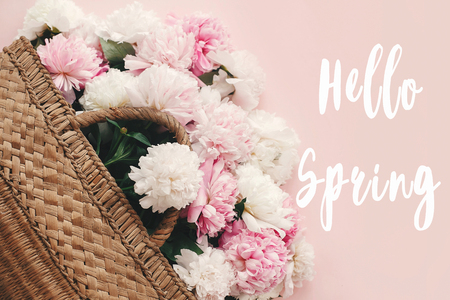 Foto de Hello Spring text sign on stylish straw rustic bag with white and pink peonies on pastel pink paper, flat lay. Stylish floral greeting card. - Imagen libre de derechos