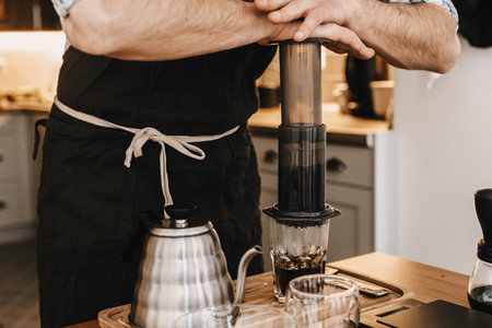 Photo pour Professional barista preparing coffee in aeropress, alternative coffee brewing method. Hands on aeropress and glass cup, scales, manual grinder, coffee beans, kettle on wooden table - image libre de droit