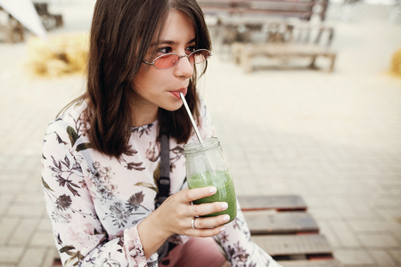 Foto de Stylish hipster boho girl drinking spinach smoothie in glass jar with metal reusable straw at street food festival. Happy woman in sunglasses with healthy drink in summer street. Zero waste - Imagen libre de derechos