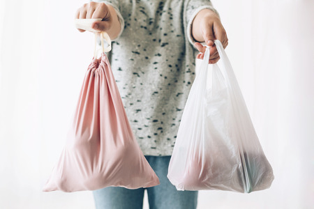 Photo pour Woman holding in one hand groceries in reusable eco bag and in other vegetables in plastic polyethylene bag. Choose plastic free items. Ban single use plastic. Zero Waste shopping concept. - image libre de droit