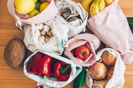 Photo for Fresh groceries in eco cotton bags on wooden table, flat lay. Zero Waste shopping concept. Vegetables from market in reusable bags. Ban single use plastic. Sustainable lifestyle - Royalty Free Image