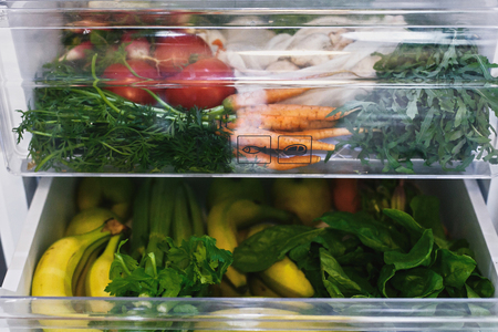 Foto de Zero waste grocery in fridge. Fresh vegetables in opened drawer in refrigerator. Plastic free carrots,tomatoes, mushrooms,bananas,salad, celery, apples, zero waste shopping. Grocery delivery - Imagen libre de derechos
