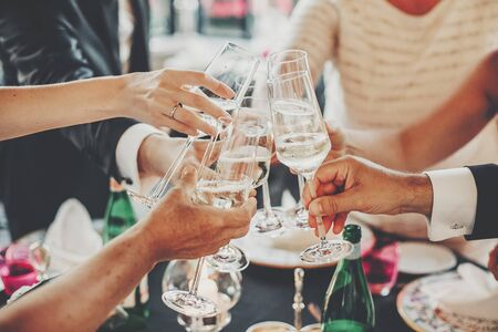 Photo pour Hands toasting with champagne glasses at wedding reception outdoors in the evening. Family and friends clinking glasses and cheering with alcohol at delicious feast celebration. Christmas party - image libre de droit