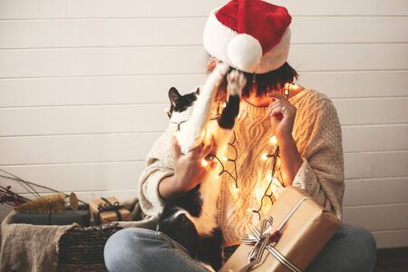 Cute cat playing with santa hat on stylish happy girl in festive christmas lights on background of modern presents. Young hipster woman in cozy sweater playing with kitty. Happy Holidays