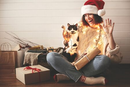 Photo for Happy Holidays. Stylish happy girl in santa hat  and cute cat waving hand and paw in festive christmas lights on background of modern presents. Young hipster woman playing with kitty. - Royalty Free Image