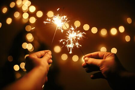 Foto de Glowing sparklers in hands on background of golden christmas tree lights, couple celebrating in dark festive room. Happy New Year. Space for text. Fireworks burning in hands. Happy Holidays - Imagen libre de derechos