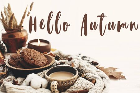 Foto de Hello Autumn text, fall greeting sign on coffee cup, chocolate cookies, candle and fall leaves, cotton, cinnamon, anise, acorns, nuts on white knitted sweater. Hygge lifestyle - Imagen libre de derechos