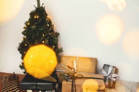 Photo for Christmas tree with festive stylish gifts in golden lights bokeh in white room. Merry Christmas.Winter holidays preparation. Copy space. Happy Holidays. Season's Greeting - Royalty Free Image
