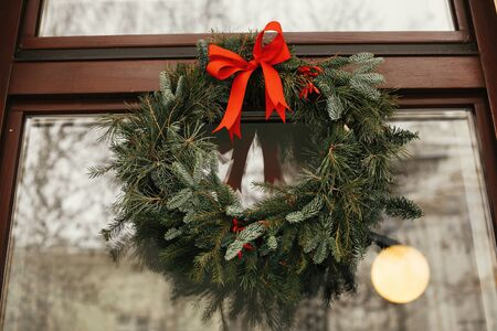 Photo pour Stylish christmas wreath with red bow and berries at front of store at holiday market in city street. Space for text. Rustic decoration. Christmas street decor. - image libre de droit