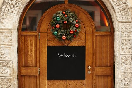 Foto de Christmas street decor. Stylish christmas wreath with red and green baubles and empty board with copy space on rustic wooden doors at holiday market in city street. Space for text.  template - Imagen libre de derechos