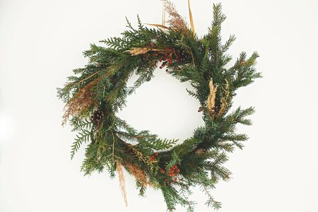 Photo pour Christmas rustic wreath. Creative rural christmas wreath with fir branches, berries, pine cones and herbs hanging on white wall in room. Copy space. Season's greetings. - image libre de droit