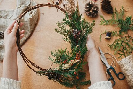 Photo for Hands holding rustic christmas wreath with pine cones, berries, fir branches, thread, scissors on wooden table.  Authentic rural wreath. Christmas wreath workshop. - Royalty Free Image