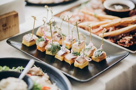Foto de Delicious food table at wedding reception. Fish finger appetizers with onion on table at wedding or christmas feast. Luxury catering concept - Imagen libre de derechos