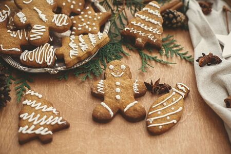 Photo pour Christmas gingerbread man,  cookies on vintage plate and anise, cinnamon, pine cones and cedar branches on rustic table. Baked traditional gingerbread cookies. Seasons greetings - image libre de droit