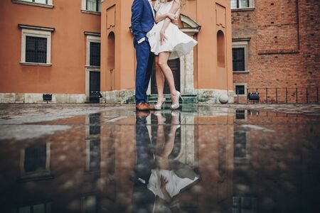 Stylish couple dancing in european city street on background of old architecture and reflection in water. Fashionable man and woman in love dancing. Traveling together in Europe