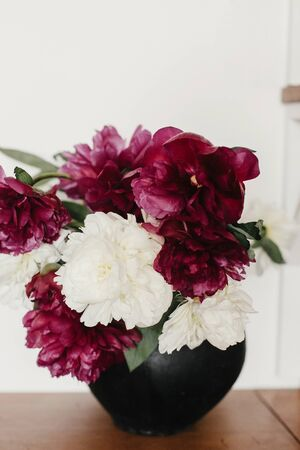 Photo pour Stylish peony bouquet in black clay vase on rustic wooden background. White and pink peonies rural still life. Hello spring wallpaper. Happy Mothers day. Space text - image libre de droit