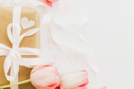 Photo pour Pink tulips with ribbon and gift box on white background, flat lay. Stylish tender image. Greeting card with space for text - image libre de droit