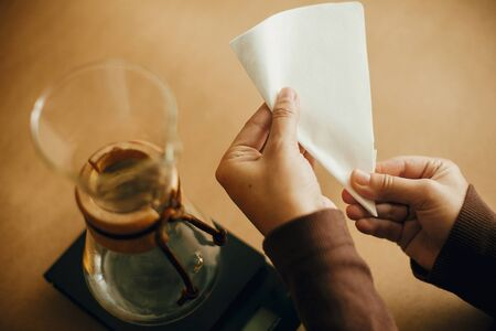 Foto de Preparing for alternative coffee brewing v60. Fold coffee filter. Hands folding paper filter for pour over and glass kettle on scale on brown background. - Imagen libre de derechos