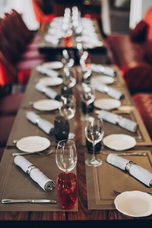 Photo pour Luxury red table setting at reception in restaurant for wine party or wedding. Stylish glasses for wine, plates with napkin, cutlery on table. Modern red catering service. Christmas feast - image libre de droit