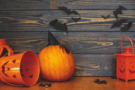 Foto de Pumpkin with spider and witch hat, Jack o lantern candy bucket and bats on dark background. Handmade holiday decorations, celebrating halloween at home. Happy Halloween! - Imagen libre de derechos