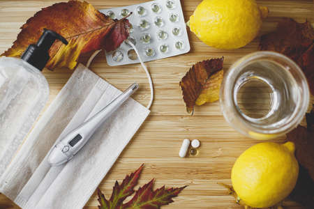 Photo pour Supporting immune system in season of autumn flu or coronavirus, concept. Vitamin D, vitamin C and zinc pills on wooden table with face mask, disinfection gel, lemons, thermometer and fall leaves - image libre de droit