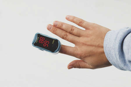 Photo pour Pulse Oximeter on female hand on white background, measuring blood oxygen level. Portable Oximeter Fingertip tests oxygen saturation, detecting COVID-19 at home - image libre de droit