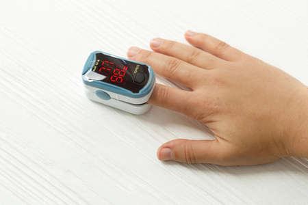 Photo pour Pulse Oximeter on adult hand on white background, measuring blood oxygen level. Portable Oximeter Fingertip tests oxygen saturation. Low oxygen levels show injury of lungs and pneumonia by virus - image libre de droit