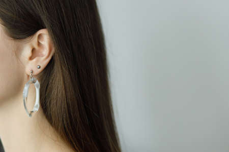 Foto de Beautiful sensual woman with modern geometric earring, close up view. Space for text. Fashionable female with unusual fused glass accessories. Beauty and care concept - Imagen libre de derechos