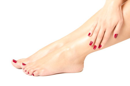Beautiful female feet and hands with red manicure isolated on white backgroundの写真素材