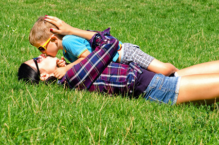 Young mother and son kissing lying on the lawn
