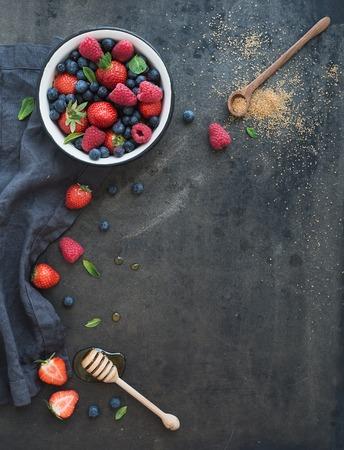 Strawberries, raspberries, blueberries and mint leaves, honey, cane sugar, dark grunge background, top view, copy space