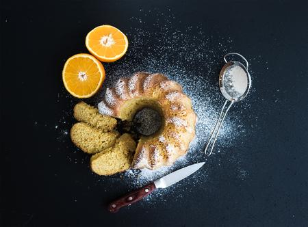 Moist orange bundt yoghurt cake with sugar powder, dark grunge background. Top view