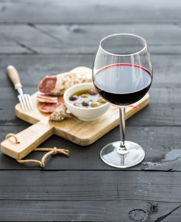 Wine appetizer set. Glass of red wine, French sausage and olives on black wooden backdrop, selective focus