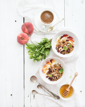 Healthy breakfast. Bowl of oat granola with yogurt, fresh fruit, mint and honey. Cup of coffee, vintage silverware. Top view, copy space
