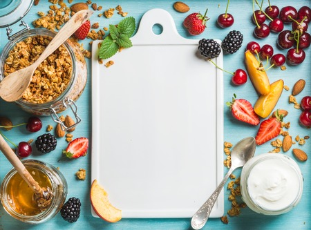 Photo pour Healthy breakfast ingredients. Oat granola in open glass jar, yogurt, fruit, berries, honey and mint on blue background with white ceramic board in center, top view, copy space - image libre de droit