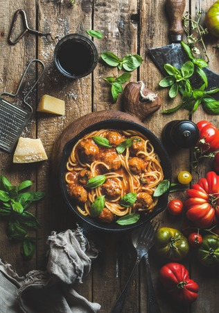 Italian pasta spaghetti with tomato sauce and meatballs in cast iron pan with Parmesan cheese, fresh basil, tomatoes and glass of wine over old rustic wooden background. Top view, vertical compositionの写真素材
