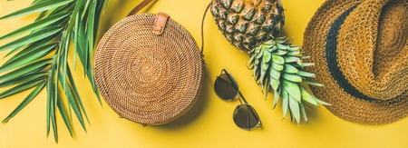 Photo for Colorful summer female fashion outfit flat-lay. Straw hat, bamboo bag, sunglasses, palm branches, pineapple over yellow background, top view, wide composition. Summer fashion, holiday concept - Royalty Free Image