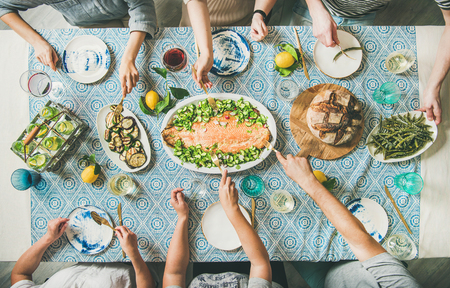 Foto de Family or friends summer party or seafood dinner. Flat-lay of group of mutinational people with different skin color at big table eating delicious food together. Summer gathering or celebration - Imagen libre de derechos