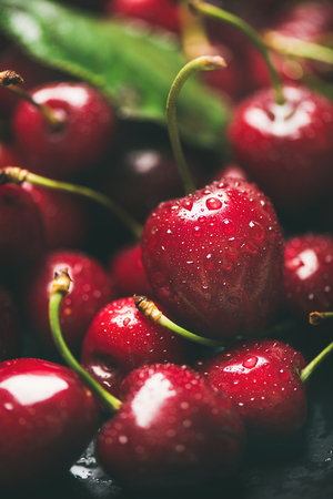 Fresh sweet cherry texture, wallpaper and background. Wet sweet cherries with leaves on dark background, selective focus, close-up, vertical composition. Summer food or local market produce concept
