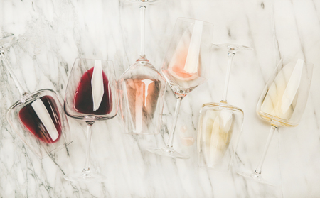 Photo pour Flat-lay of red, rose and white wine in glasses and corkscrews over grey marble background, top view. Bojole nouveau, wine bar, winery, wine degustation concept - image libre de droit