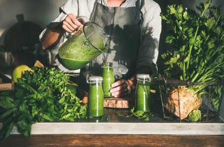 Foto de Making green detox take-away smoothie. Woman in linen apron pouring green smoothie drink from blender to bottle surrounded with vegetables and greens. Healthy, clean eating, weight loss food concept - Imagen libre de derechos
