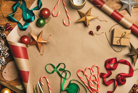 Foto de Getting ready for Christmas or New Year holiday. Flat-lay of decorations, ribbons, gift paper, door wreath, glittering balls, candy canes, top view, copy space. Christmas festive mood - Imagen libre de derechos