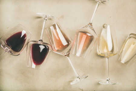 Photo pour Flat-lay of red, rose and white wine in glasses over grey concrete - image libre de droit