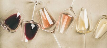 Foto de Flat-lay of red, rose and white wine in glasses over grey concrete - Imagen libre de derechos