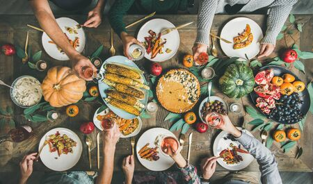 Photo pour Vegan or vegetarian Thanksgiving, Friendsgiving holiday celebration. Flat-lay of friends eating and feasting at Thanksgiving Day table with pumpkin pie, vegetables, fruit and rose wine, top view - image libre de droit