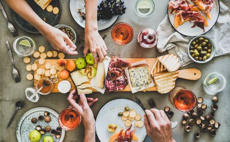 Photo pour Mid-summer picnic with wine and snacks. Flat-lay of charcuterie and cheese board, rose wine, nuts, olives and peoples hands over concrete table background, top view. Family, friends holiday gathering - image libre de droit