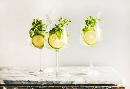 Photo for Hugo Sparkling wine cocktail with fresh mint and lime in glasses with eco-friendly straws over white marble counter, selective focus. Cold refreshing summer alcoholic drink - Royalty Free Image