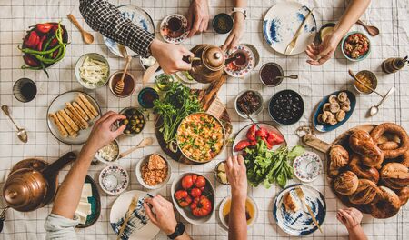 Flat-lay of family having Turkish breakfast with pastries, vegetables, greens, spreads, cheeses, fried eggs, jams and tea in tulip glasses and copper teapots over pastel chekered linen tablecloth
