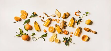 Photo pour Immune boosting natural vitamin health defending drink to resist virus. Flat-lay of fresh turmeric, ginger and citrus juice shots over white background, top view. Vegan Immunity system booster - image libre de droit